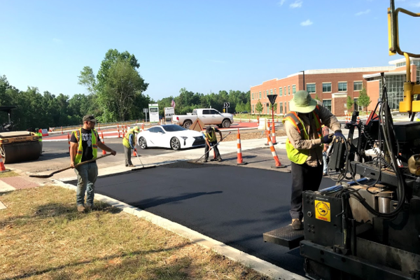 Workers smoothing blacktop on roadway