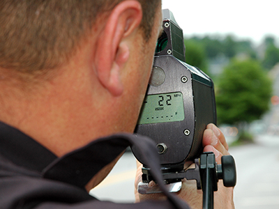 Officer using speed detection device